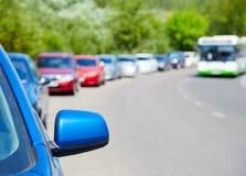 Auto's op de kant van de weg en de bus worden geparkeerd die stock afbeeldingen