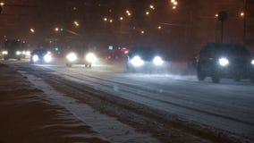 Auto's op de stadsweg in een sneeuwstorm bij nacht stock videobeelden