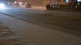 Auto's op de weg in een sneeuwstorm bij nacht stock videobeelden