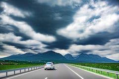 Auto's op het spoor tegen de achtergrond van bergen en bewolkte hemel stock foto
