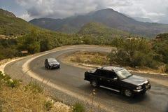 Auto's op kronkelige weg in bergen Stock Fotografie