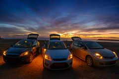 Auto's tegen zonsondergangachtergrond royalty-vrije stock afbeelding