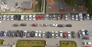 Auto's voor high-rise de bouw worden geparkeerd die Stock Afbeeldingen