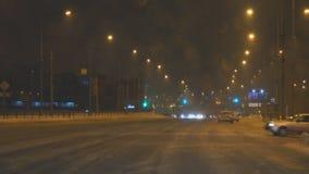 Auto'saandrijving door kruispunten in de stad van de de winternacht stock videobeelden