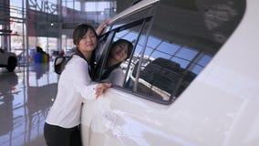 Auto salão de beleza, aparência asiática da mulher alegre do consumidor com o prazer que afaga o carro novo que sorri delicadamen filme
