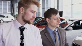 In auto salon consultant shows buyer new models of cars. slow motion. In auto salon stylish consultant shows male buyer new and worn out models of cars. slow stock video