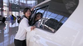 Auto salon, merry consumer woman asian appearance with delight stroking new car gently smiling at dealership. Close-up stock footage