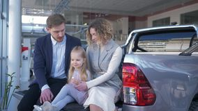 Auto salon, young family with child chooses vehicle and communicate with each other while sitting in trunk at car