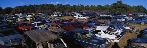 This is an auto salvage yard. The cars here are either crashed vehicles or no longer in use. They are wrecks all parked side by si Royalty Free Stock Photography