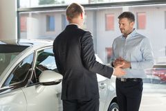 Auto seller discussing with client Royalty Free Stock Image