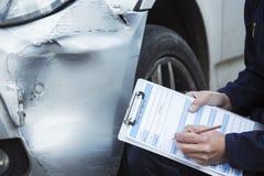 Auto seminariummekanikerInspecting Damage To bil och fyllning i R royaltyfri foto