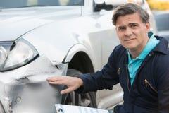 Auto seminariummekanikerInspecting Damage To bil och fyllning i R arkivbilder