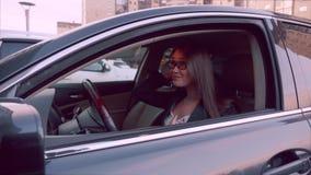 A auto senhora olha na opinião traseira do espelho para a composição da verificação no carro Mulher no carro estacionado video estoque