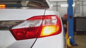 Auto serviço - verificando faróis traseiros do carro Fotos de Stock
