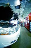 Auto Service. In the Auto Service. Damaged White Vehicle with Open Hood. Large Warehouse / Dealer Service Area Royalty Free Stock Photos