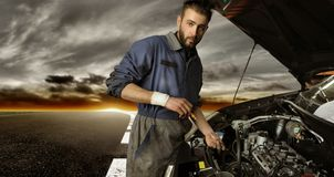 Auto service. Auto mechanic checking car on the street Royalty Free Stock Photography
