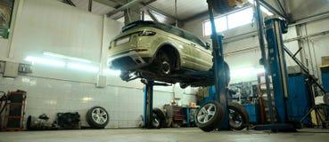 Auto-Service-Center Fahrzeug gehoben auf Aufzug an der Wartungsstation Reparatur und Kontrolle Auomobile stockfotos