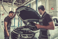 At the auto service. Handsome young auto mechanics in uniform are examining car while working in auto service Royalty Free Stock Photos