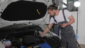 Auto service, holding digital tablet in his hands, mechanician stands near open hood automobile, control electric wiring stock footage