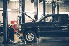 Auto Service Interior. Large Auto Service Warehouse Interior and Pickup Truck Under Maintenance Royalty Free Stock Image