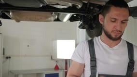 Auto service, Man mechanician, Inspects machine stock video