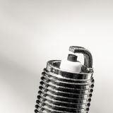 Auto service. New spark plug as spare part of car. Royalty Free Stock Images