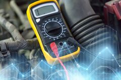 Multimeter or voltmeter testing car battery. Auto service, repair and maintenance concept - digital multimeter or voltmeter testing car battery stock image