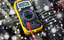 Multimeter or voltmeter testing car battery. Auto service, repair and maintenance concept - digital multimeter or voltmeter testing car battery over snow royalty free stock images