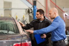 Auto mechanic and customer at car shop Royalty Free Stock Images