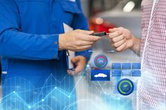 Auto mechanic giving car key to man at workshop Royalty Free Stock Image