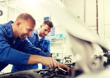Mechanic men with wrench repairing car at workshop stock images