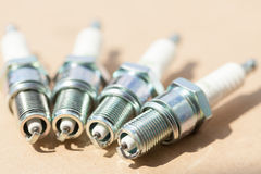 Auto service. Set of spark plugs as spare part of car. Stock Photos