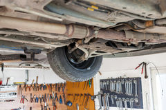 Auto service shop has lift for easy working on underside of car Royalty Free Stock Images