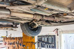 Auto service shop has lift for easy working on underside of car Royalty Free Stock Photography