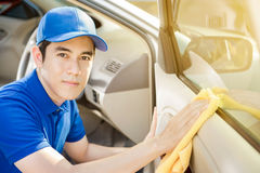 Auto service staff cleaning car door Stock Photo
