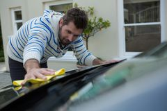 Auto service staff cleaning a car with duster. Male auto service staff cleaning a car with duster Royalty Free Stock Image