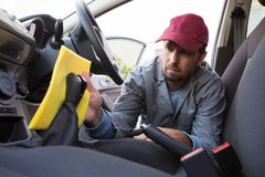 Auto service staff cleaning car interior. Male auto service staff cleaning car interior Stock Photography