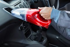 Auto service staff cleaning car with portable vacuum Royalty Free Stock Image
