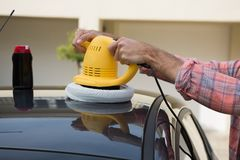 Auto service staff cleaning a car with rotating wash brush. Male auto service staff cleaning a car with rotating wash brush Royalty Free Stock Photos