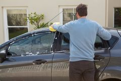Auto service staff washing a car roof with sponge Royalty Free Stock Photos