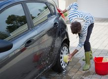 Auto service staff washing a car tyre with sponge Royalty Free Stock Photo