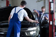 Auto service worker diagnosing car Royalty Free Stock Photo