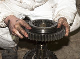 Auto service. The worker dirty hands holds a big gear in auto service Royalty Free Stock Images