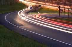 Auto'slichten in de weg bij nacht stock afbeelding