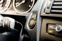 Auto start and stop button. On a modern premium car interior suggesting fuel economy, modern technology and eco friendlyness on a bright sunny day with some Royalty Free Stock Photo