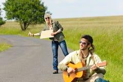 Auto-stop de la jeune route goudronnée de sac à dos de couples Photo stock