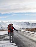 Auto-stop del viaggiatore con zaino e sacco a pelo in Islanda Fotografie Stock