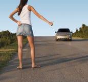 Auto-stop della ragazza sulla via immagini stock