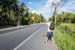 Auto-stop turistico maschio sul bordo della strada dalla strada principale immagini stock libere da diritti