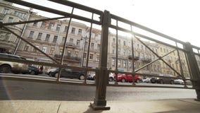Auto'stribune nog op weg met opstopping langs lange straat met gebouwen stock videobeelden
